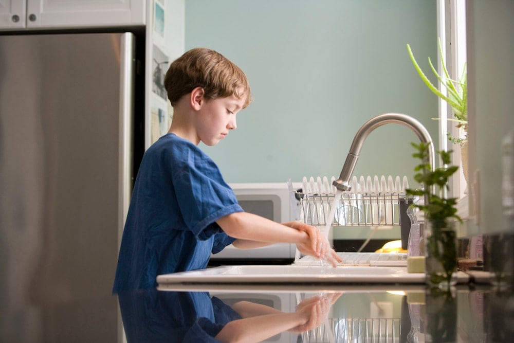 young boy washes hands at sink to prevent respiratory illnesses